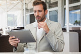 Handsome young businessman working on tablet drinking espresso