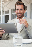 Happy young businessman working on tablet drinking espresso