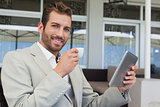 Cheerful young businessman working on tablet drinking espresso