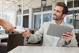 Cheerful businessman working with digital tablet taking his espresso