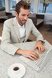 Happy businessman working with his laptop at table having coffee