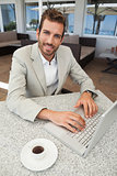 Smiling businessman working with his laptop at table having coffee