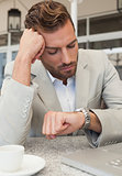 Frowning businessman looking at his watch
