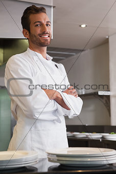 Happy young chef standing with arms crossed behind counter