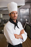 Serious chef looking at camera with arms crossed holding ladle