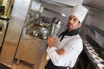 Focused chef looking at camera with arms crossed holding ladle