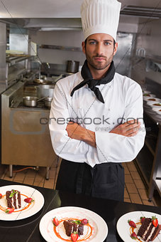 Focused chef looking at camera behind counter of desserts