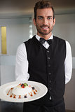 Smiling waiter showing plate of dessert to camera