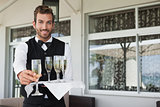 Handsome smiling waiter offering flute of champagne