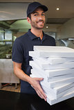 Happy pizza delivery man holding many pizza boxes