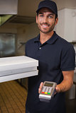 Happy pizza delivery man showing credit card machine