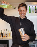 Happy bartender preparing a cocktail