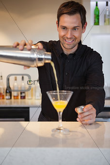Smiling bartender pouring cocktail into glass