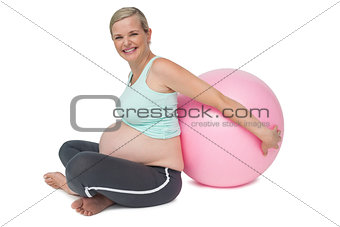 Pregnant woman leaning against pink exercise ball