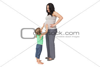 Little girl touching her mothers baby bump