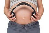 Pregnant woman holding headphones over bump