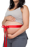Pregnant woman with a red ribbon around her bump