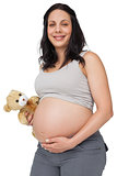 Pregnant woman holding a teddy smiling at camera