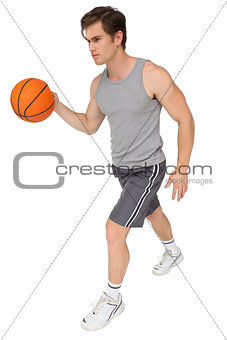 Fit man playing basketball