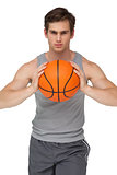 Fit man holding basketball about to throw to camera