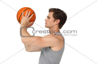 Athletic man holding basketball about to shoot