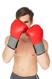 Muscly man wearing red boxing gloves in guard position