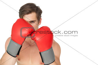 Tough man wearing red boxing gloves in guard position
