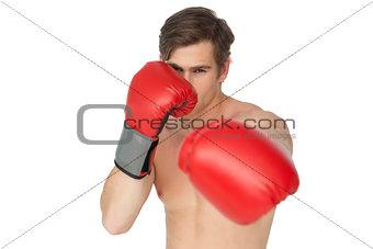 Tough man wearing red boxing gloves punching to camera