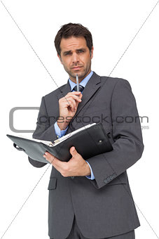 Handsome thinking businessman holding his diary