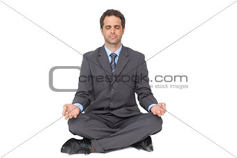 Calm businessman meditating in lotus pose
