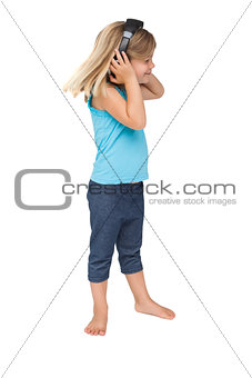 Cute little girl listening to music and dancing