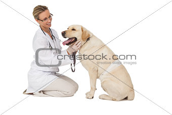 Pretty vet petting yellow labrador dog