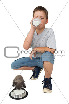 Cute little boy and grey kitten both drinking milk