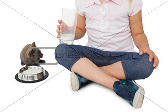 Cute girl and grey kitten both having milk