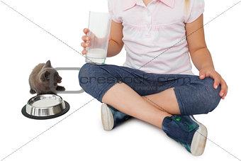 Cute girl and grey kitten both having milk