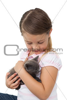 Cute girl cuddling grey kitten
