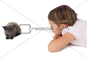 Cute girl looking at grey kitten lying on floor