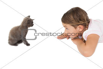 Little girl looking at grey kitten sitting on floor