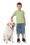 Cute little boy standing with his labrador dog smiling at camera