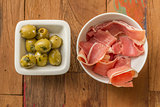 Typical Spanish tapas: serrano ham and green olives