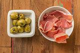 Typical Spanish tapas: serrano ham and green olives