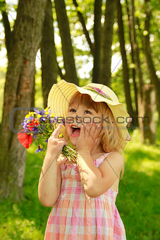 beautiful little girl in nature with a bouquet of flowers