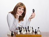 Woman with a figure of horse , at chess Board