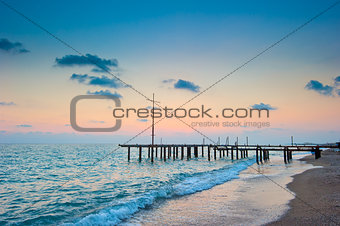 frame of the old pier on the beach at dawn