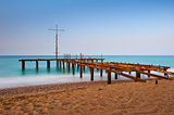 rusty skeleton of the old pier and turquoise sea