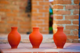 three handmade clay jug on brick wall background
