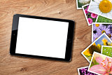 Tablet with blank screen and stack of printed pictures collage