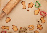 Rolling pin and gingerbread cookies on cooking paper