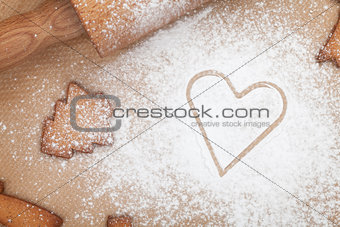 Rolling pin with flour and cookies on cooking paper