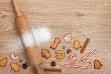 Rolling pin with flour, spices and cookies on wooden table